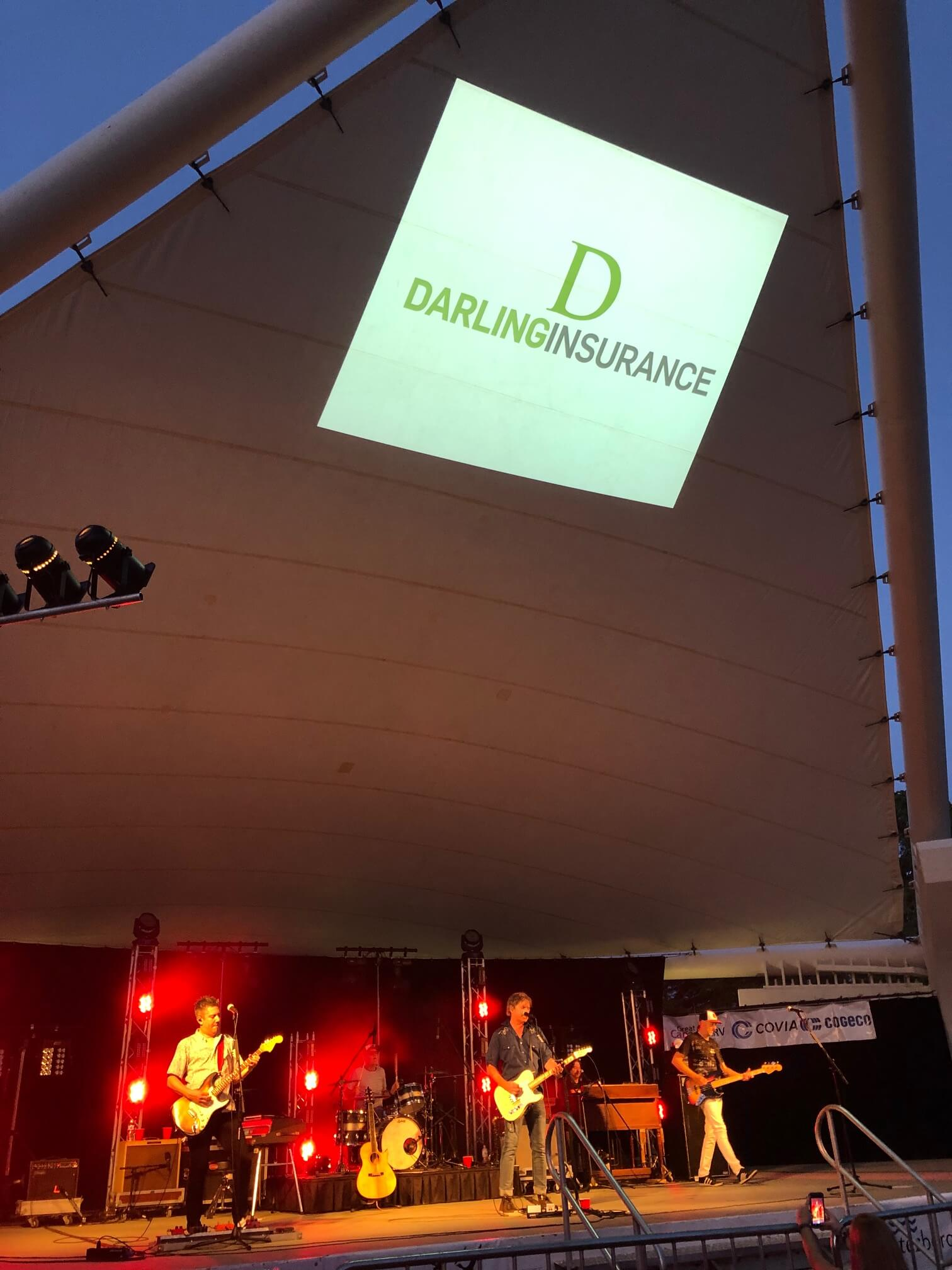 Photo of the musicfest stage with Darling Insurance's logo projected on the roof